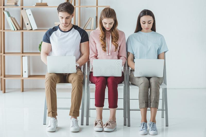 Young students sitting and studying. With laptops together stock images