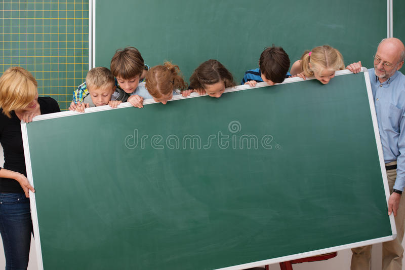 Young students and teachers holding a blackboard. Young students and their two teachers standing holding a blank blackboard all peering over the top to see what stock photo