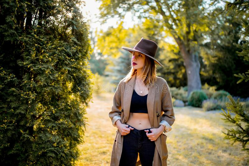 Girl in hat and clothes in a village garden in sunset time. Young style girl in hat and clothes in a village garden in sunset time royalty free stock images