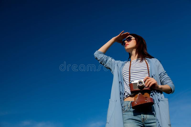 Redhead girl in modern clothes with camera royalty free stock image