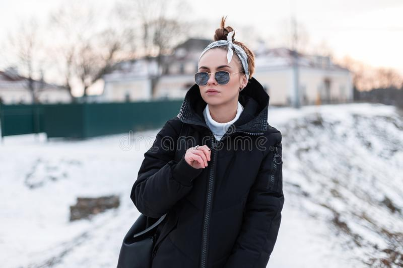 Young stylish beautiful hipster woman in black sunglasses in a stylish bandana in a trendy black jacket with a backpack royalty free stock images