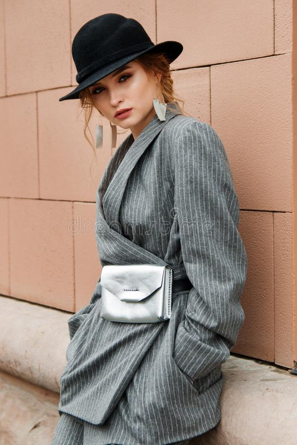 Young stylish beautiful woman fashion model is posing in street, wearing pantsuit, having purse on her waist stock photo