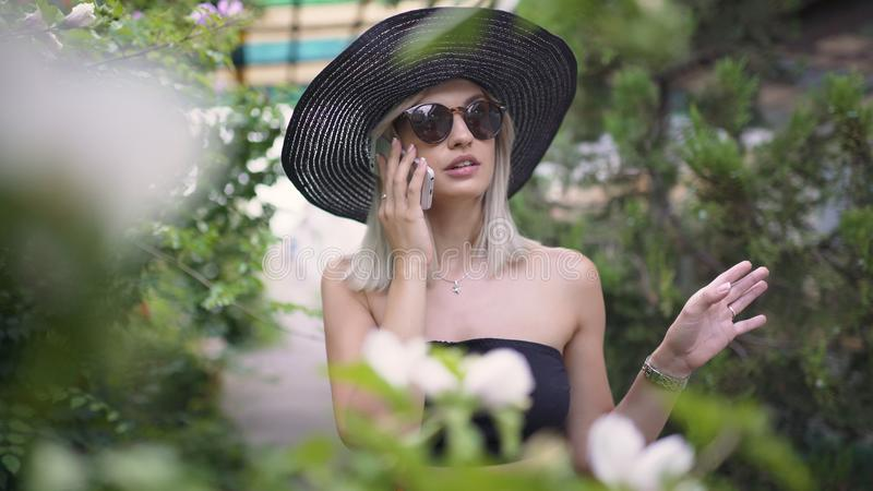 Young stylish beautiful woman in hat using a smart phone. Female talking on the phone. Beautiful stylish young blonde woman smoking cigarettes outdoors in han stock image