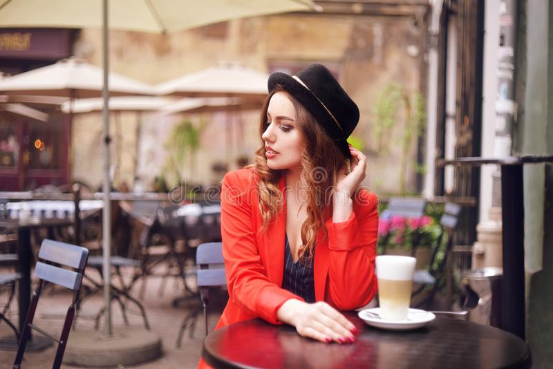 Young stylish beautiful woman sitting in city cafe in red jacket, street style, drinking aromatic coffee. Elegant girl in hat royalty free stock photos