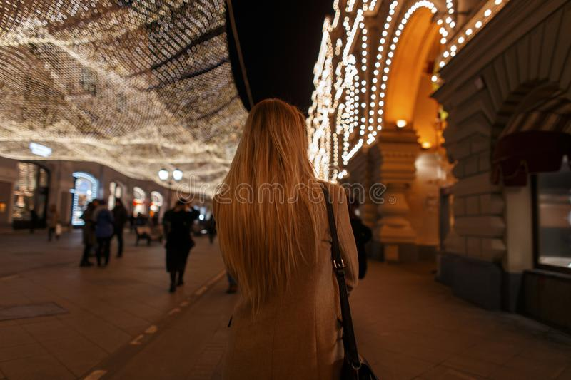 Young stylish blond woman with long hair in a fashionable coat stock images