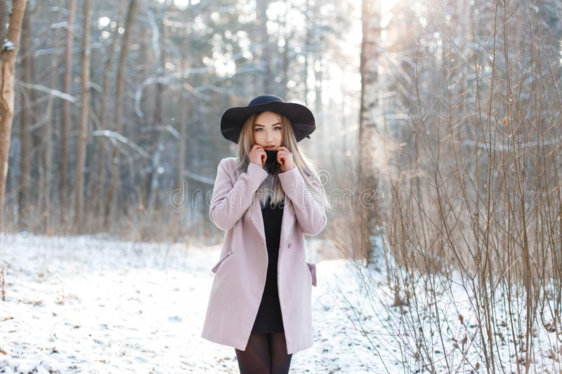 Young stylish blonde woman in an elegant black hat in a pink stylish coat in a black fashionable dress royalty free stock photos