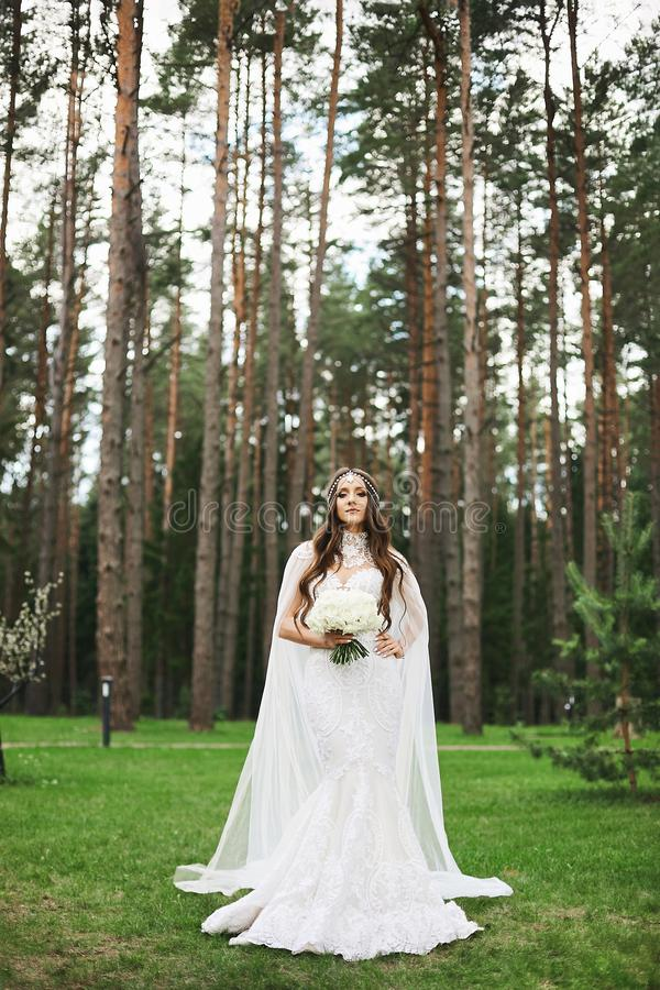 Young stylish bride with jewelry in her hairstyle wearing in lace wedding dress keeping a bouquet of flowers and posing royalty free stock photos