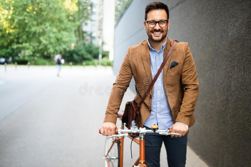 Happy young stylish businessman going to work by bike stock images