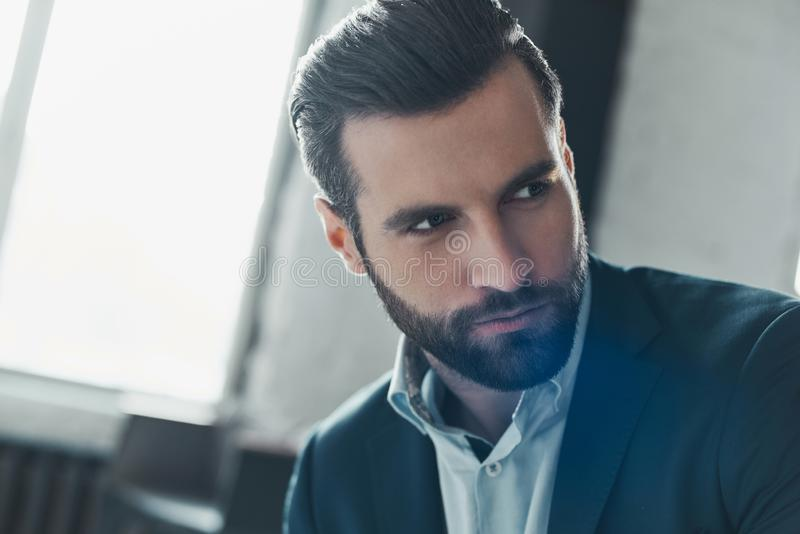 Young stylish businessman leader indoors at office looking aside. Young bearded stylish businessman leader indoors at office looking aside serious confident face stock photo