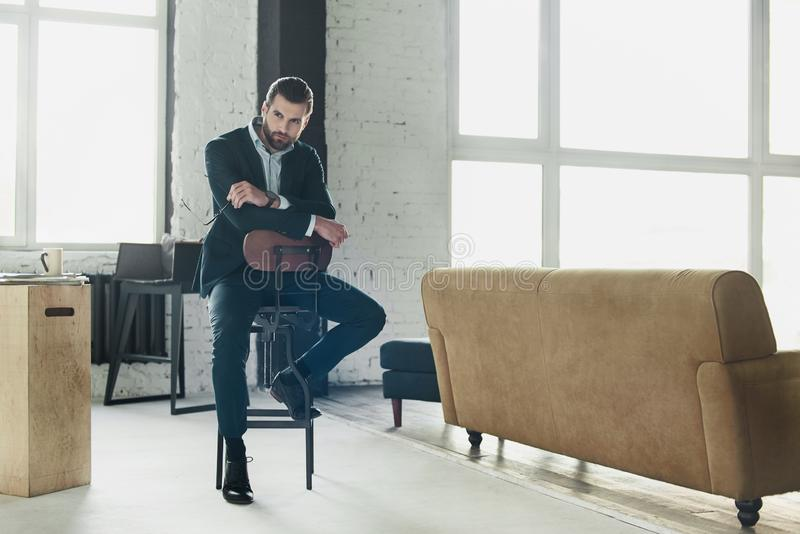 Young stylish businessman leader indoors at office sitting. Young bearded stylish businessman leader indoors at office candid sitting on chair looking aside royalty free stock photos