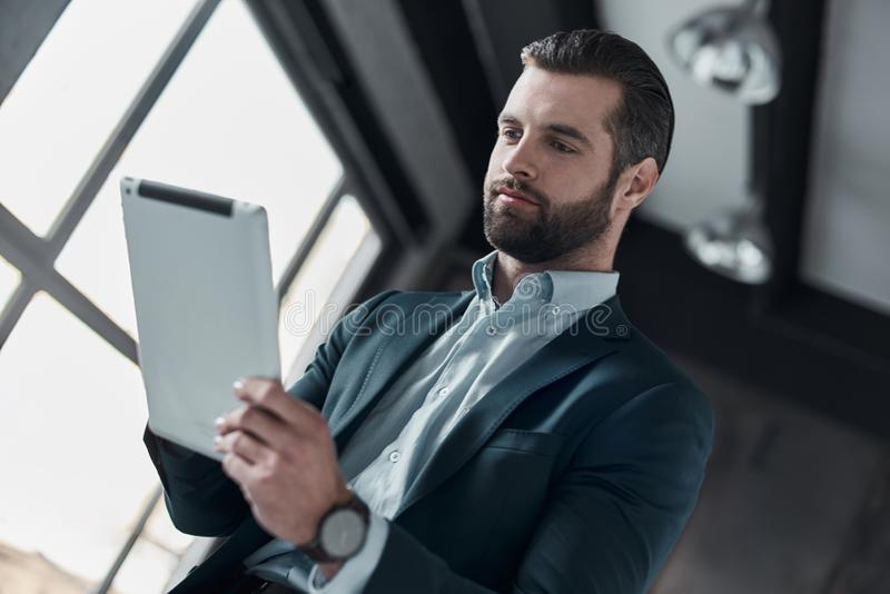 Young stylish businessman leader indoors at office using digital. Young bearded stylish businessman leader indoors at office bottom view using digital tablet royalty free stock image