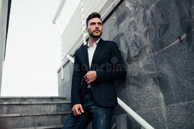 Young stylish businessman man with a beard in a fashionable suit and jeans. Modern image of business youth. It stands on the royalty free stock images