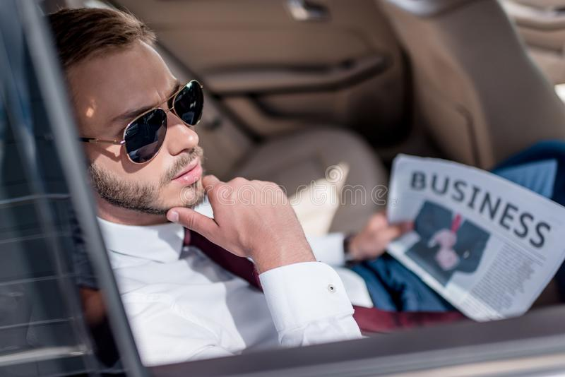 Young stylish businessman in sunglasses with business newspaper on backseat. Of car stock images