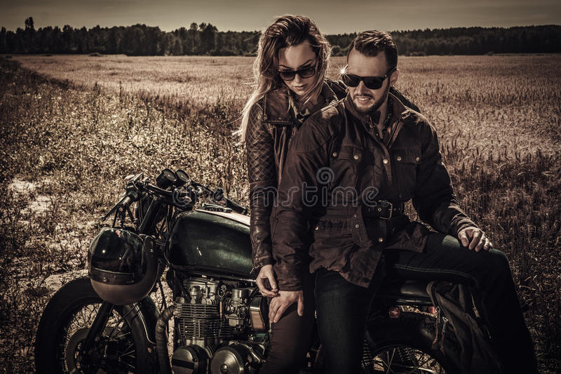 Young, stylish cafe racer couple on vintage custom motorcycles in field.  stock photo