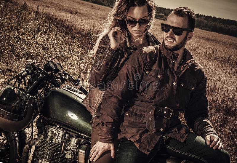 Young, stylish cafe racer couple on vintage custom motorcycles in field.  royalty free stock image