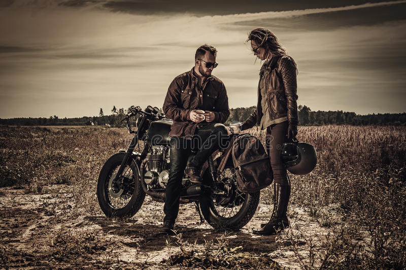 Young, stylish cafe racer couple on vintage custom motorcycles in field.  stock images