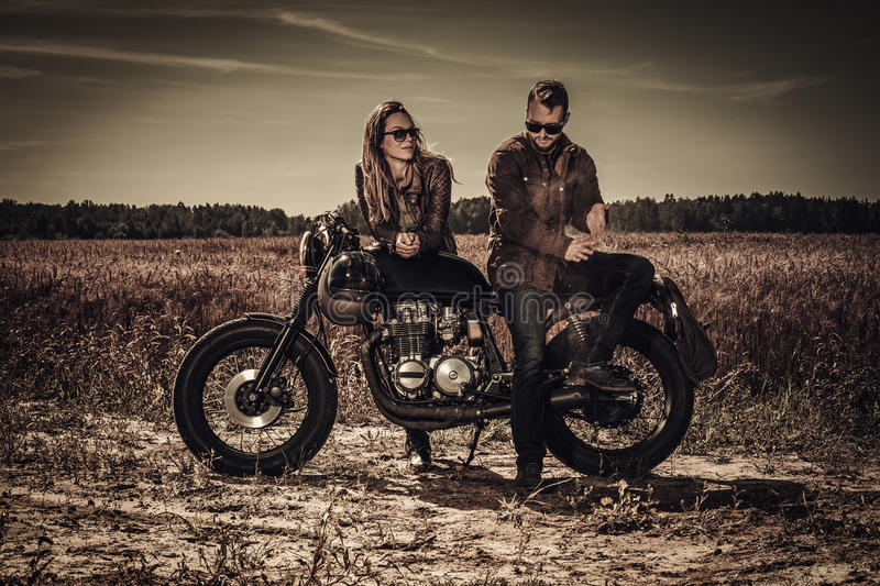 Young, stylish cafe racer couple on vintage custom motorcycles in field.  royalty free stock photography