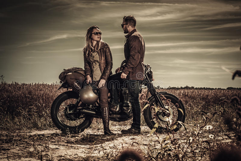 Young, stylish cafe racer couple on vintage custom motorcycles in field.  royalty free stock images