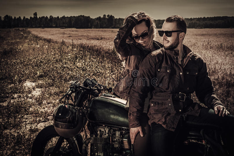 Young, stylish cafe racer couple on vintage custom motorcycles in field.  stock photography
