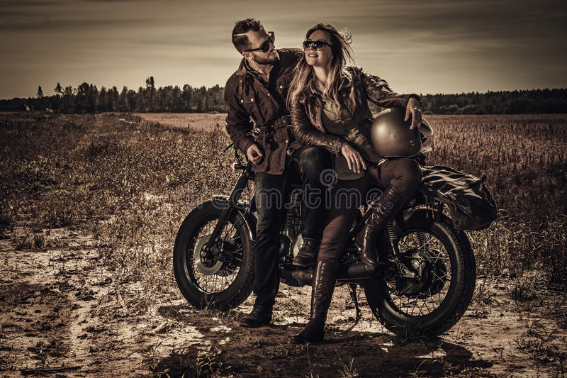 Young, stylish cafe racer couple on vintage custom motorcycles in field.  stock photos