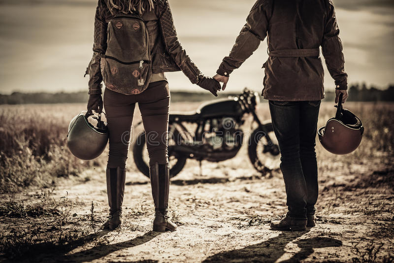 Young, stylish cafe racer couple and vintage custom motorcycles in field.  royalty free stock photos