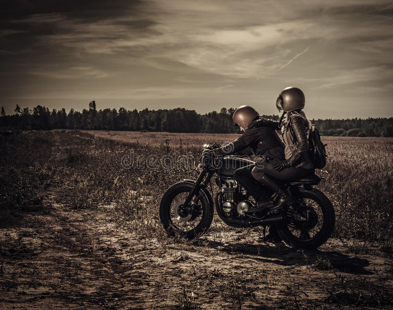 Young, stylish cafe racer couple on vintage custom motorcycles in field.  stock image
