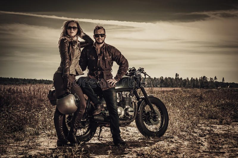 Young, stylish cafe racer couple on vintage custom motorcycles in field.  royalty free stock photo