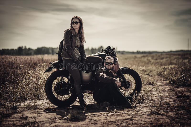 Young, stylish cafe racer couple on vintage custom motorcycles in field.  royalty free stock photos