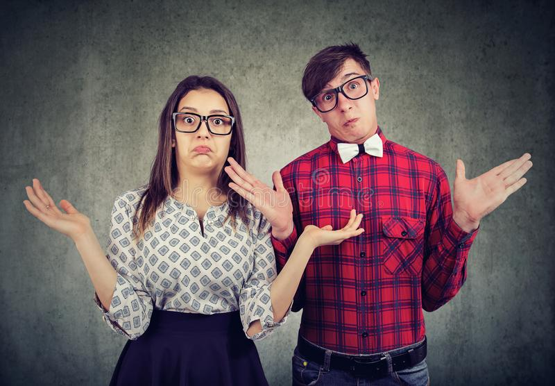Dubious couple shrugging with shoulders stock photos