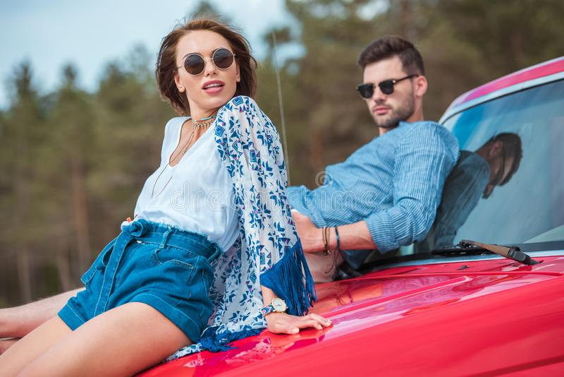 young stylish couple in sunglasses sitting on red royalty free stock photos