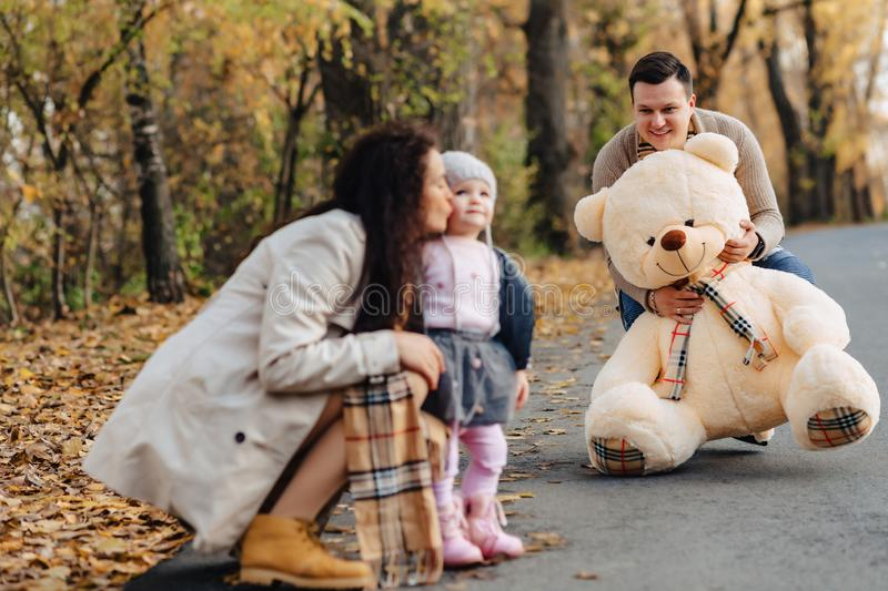 Young family with little daughter at autumn park road present bi stock photography