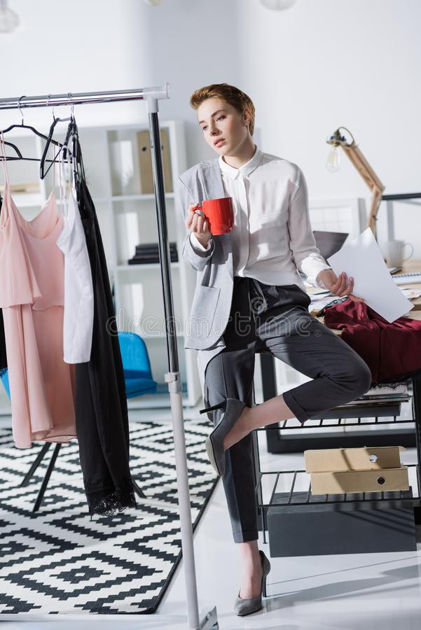 Young stylish fashion designer sitting on desk at office and looking. At dresses stock image