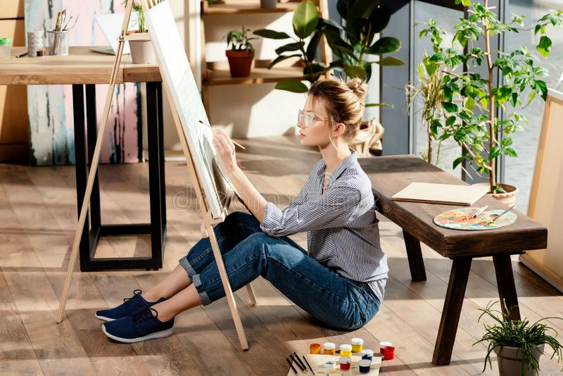Young stylish female artist in eyeglasses painting. On easel stock photography