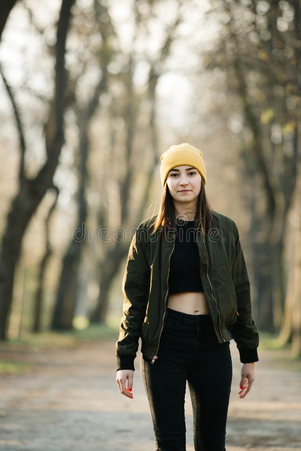 Young stylish girl with belly top walking on an avenue. stock photos