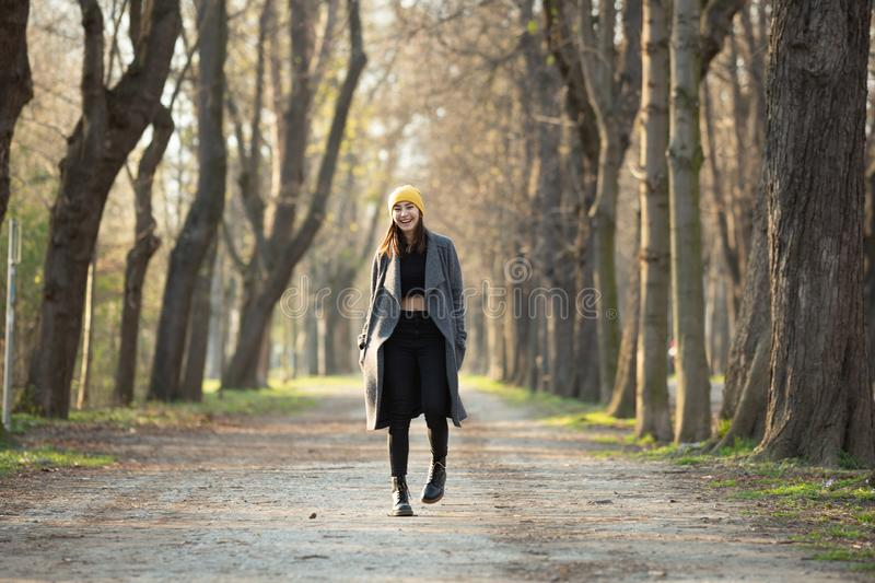 Young stylish girl with belly top walking on an avenue. royalty free stock photos