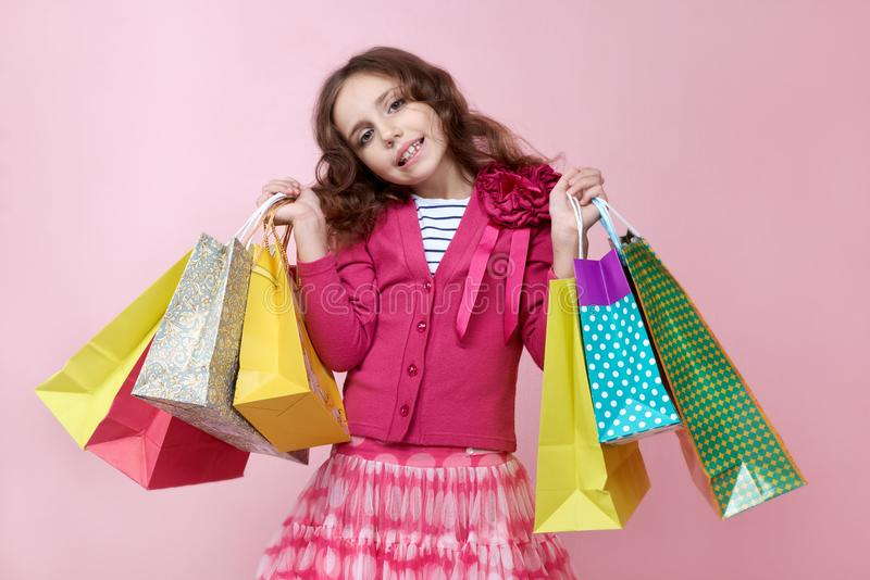 Young stylish girl Flirty teenager posing for a portrait on isolated background holding many shopping bags with a bold smile on h. Er face stock images