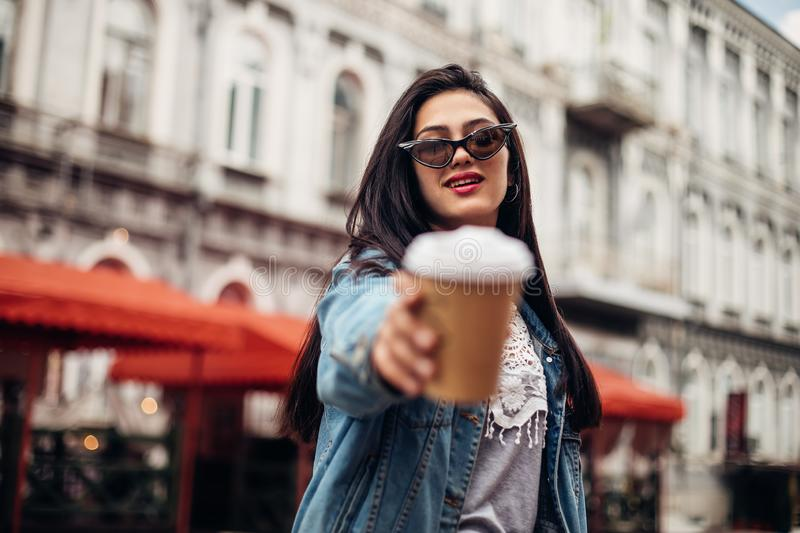Young stylish girl holds coffee to go. Wearing fashionable glasses and denim jacket.Keeps coffee. concept of street fashion stock photos