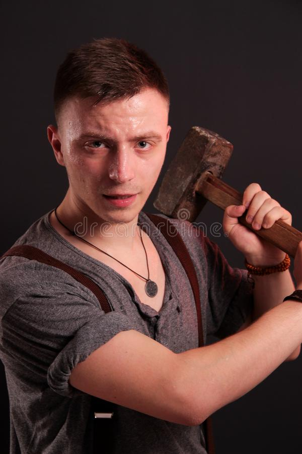 A young stylish guy with a big hammer stock image