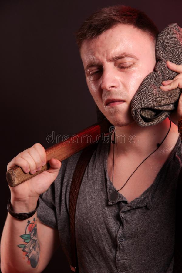 A young stylish guy with a big hammer stock images