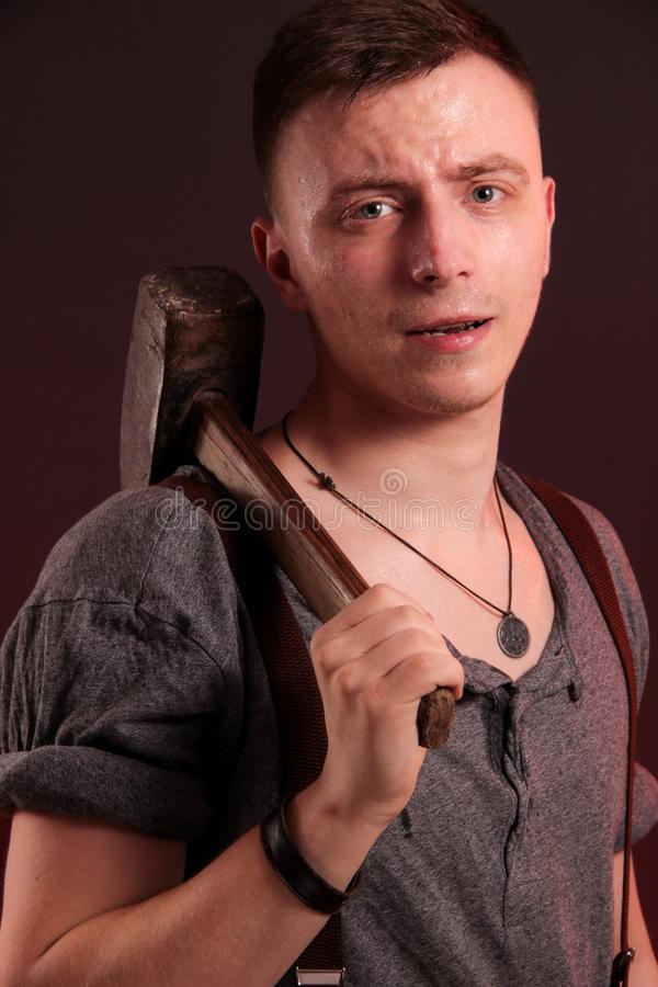 A young stylish guy with a big hammer royalty free stock image