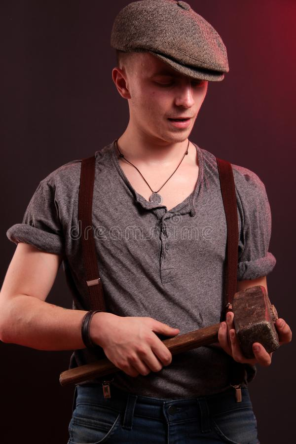 A young stylish guy with a big hammer stock photo