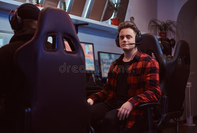 A young stylish guy wearing a checkered shirt and headset sitting on a gamer chair and looking at a camera in a gaming. A young stylish gamer wearing a checkered royalty free stock photos