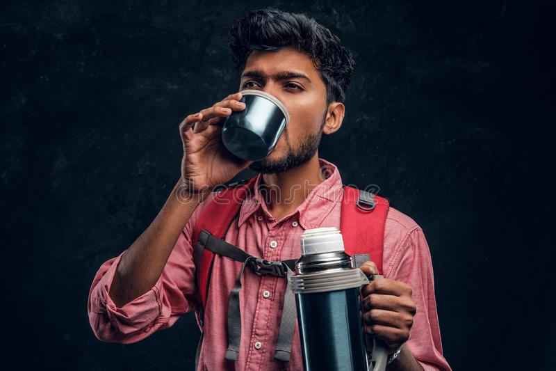 Young stylish hiker with backpack drinking a tea from a thermos. Studio photo against a dark textured wall royalty free stock image