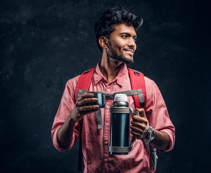 Young stylish hiker with backpack holding a cup with tea while smiling and looking sideways. Studio photo against a dark textured wall royalty free stock photography