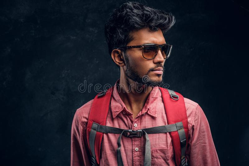 Young stylish hiker with backpack wearing sunglasses looking sideways. Studio photo against a dark textured wall royalty free stock photo