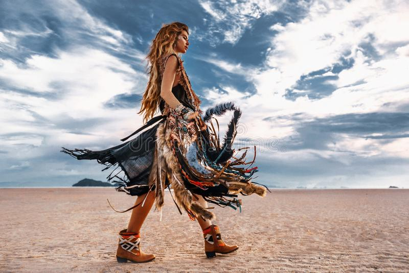 Young stylish hippie woman with big stylish bag walking on the beach at sunset stock photo
