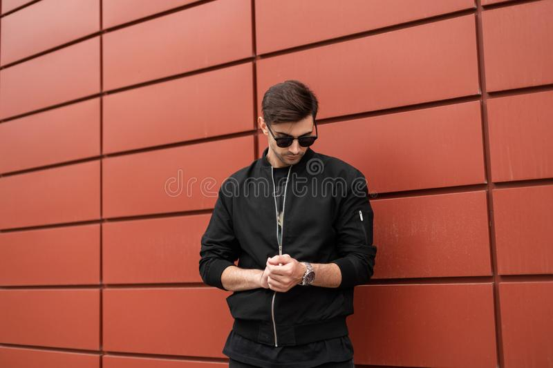 Young stylish hipster man in black jacket in stylish sunglasses straightens silver clock. Fashionable handsome model guy outdoors. In the city near a red royalty free stock images