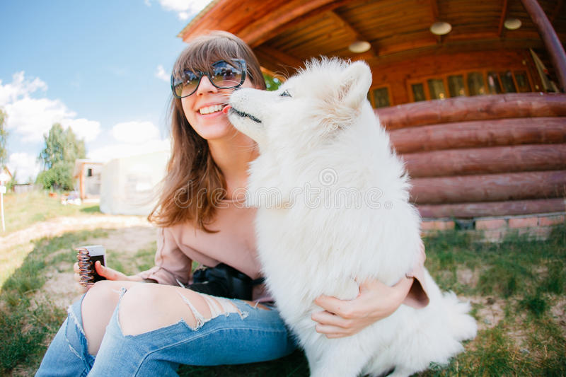 Young stylish hipster woman girl playing white kid-skin dog in country side royalty free stock photo
