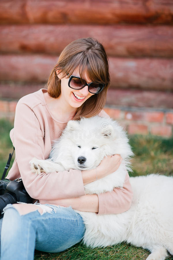 Young stylish hipster woman girl playing white kid-skin dog in country side stock photography