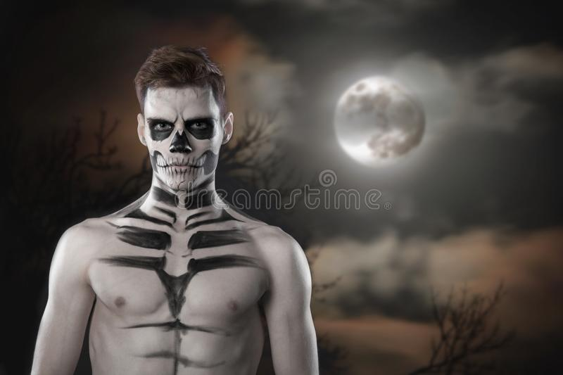 Young stylish man with art grimm for hallowen party. Fashion body art. Face art royalty free stock photo